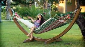 Mulher moreno de sorriso nova no chapéu relaxado e que balança na rede na praia tropical filme