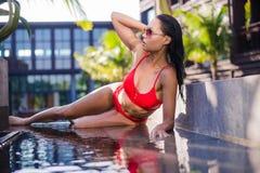 Mulher moreno de sorriso que senta-se pela associação com água azul clara perto das palmeiras Assento na borda da piscina imagens de stock royalty free