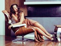 Mulher moreno de Yong da beleza que senta-se perto da chaminé em casa, winte imagens de stock royalty free