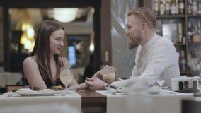 Mulher moreno do encanto do retrato e um homem louro farpado considerável que senta-se na tabela na frente de se O homem video estoque