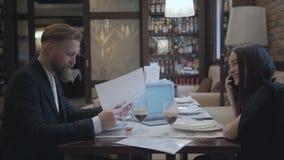 Mulher moreno e homem farpado louro que sentam-se na tabela no funcionamento do café e na cerveja bebendo Portátil, papéis e video estoque