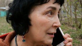 Mulher moreno elegante adulta que fala emocionalmente em seu smartphone video estoque