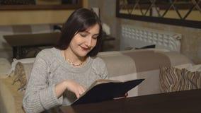 A mulher moreno em um café olha o menu imagens de stock royalty free