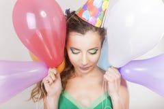Mulher moreno em um tampão do aniversário que guarda balões e sorriso Foto de Stock