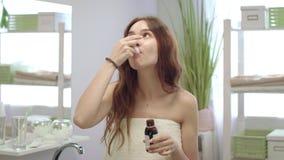 Mulher moreno envolvida na toalha que toma o xarope da tosse da cura na sala do banho vídeos de arquivo