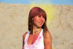 Mulher moreno fabulosa que aprecia o festival de Holi no deserto Mulher que levanta com explosão da pintura amarela imagens de stock royalty free