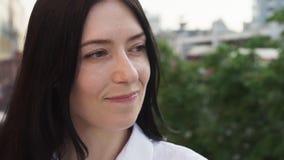 A mulher moreno feliz olha ao redor na cidade, movimento lento video estoque