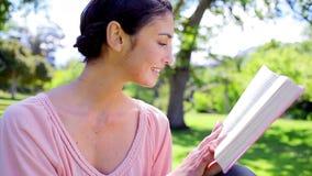Mulher moreno feliz que lê uma novela video estoque