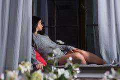 A mulher moreno grávida bonita em um vestido feito malha senta-se no Fotografia de Stock