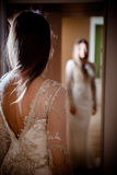 Mulher moreno lindo com cabelo longo e os olhos azuis que olham-se no espelho Imagem de Stock Royalty Free
