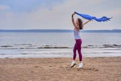 Mulher moreno magro nova no sportswear que faz a dança do esporte com um lenço azul Uma mulher é contratada na costa arenosa de u imagens de stock