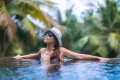 A mulher moreno magro nova toma sol na piscina tropical foto de stock