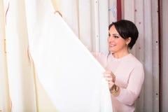 Mulher moreno na loja de matéria têxtil imagens de stock