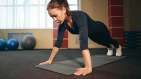 A mulher moreno no gym levanta o exercício do exercício da flexão de braço filme