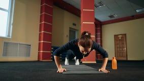 A mulher moreno no gym levanta o exercício do exercício da flexão de braço video estoque