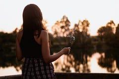 Mulher moreno no por do sol em um lago com uma vara do incenso imagem de stock