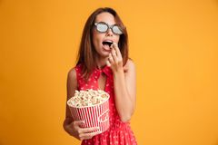 Mulher moreno nova bonita nos vidros 3d e no eatin vermelho do vestido Foto de Stock Royalty Free
