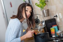Mulher moreno nova bonita que cozinha na cozinha imagens de stock