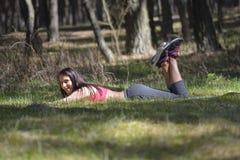 Mulher moreno nova bonita que relaxa na floresta Imagem de Stock