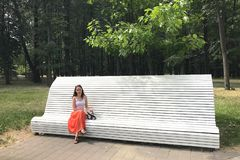 A mulher moreno nova caucasiano está sentando-se em um banco branco no parque e está olhando-se na câmera em um dia de verão enso fotografia de stock royalty free