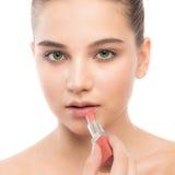 Mulher moreno nova com a cara limpa perfeita que aplica o batom Isolado em um branco Foto de Stock Royalty Free