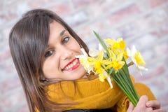 Mulher moreno nova com o ramalhete dos narcisos amarelos Fotos de Stock Royalty Free