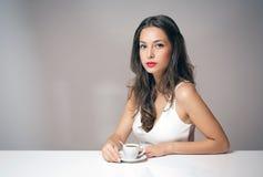 Mulher moreno nova com uma xícara de café fotografia de stock