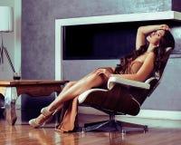 Mulher moreno nova da beleza que senta-se perto da chaminé em casa, interior luxuoso, pessoa no feriado fotos de stock royalty free