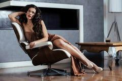 Mulher moreno nova da beleza que senta-se perto da chaminé em casa, noite morna do inverno no interior, esperando para comemorar Imagens de Stock