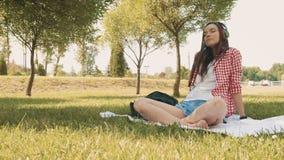 Mulher moreno nova de sorriso que escuta a música ao sentar-se na grama no parque filme