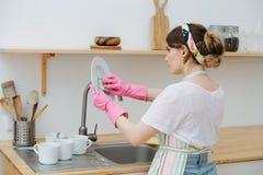A mulher moreno nova em uma cozinha est? lavando copos e pratos foto de stock royalty free