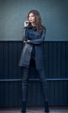 Mulher moreno nova encantador no equipamento, no revestimento e na calças de couro pretos, com obscuridade - parede cinzenta no f Fotos de Stock