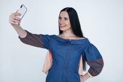 Mulher moreno nova entusiasmado que faz o selfie usando o telefone esperto Menina do estudante com cabelo longo na camisa das cal fotografia de stock royalty free