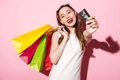 Mulher moreno nova feliz que guarda o cartão e os sacos de compras de crédito imagem de stock