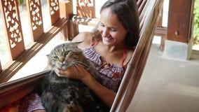 Mulher moreno nova feliz que relaxa em uma rede com o gato de Maine Coon no jardim no dia de verão ensolarado, movimento lento vídeos de arquivo