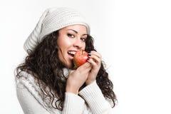 Mulher moreno nova na moda que morde uma maçã Imagem de Stock Royalty Free