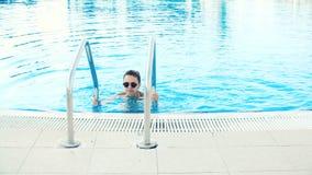 A mulher moreno nova no biquini e nos óculos de sol sai da piscina no dia de verão ensolarado filme