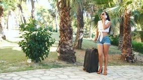 Mulher moreno nova no short, nos óculos de sol e nos saltos com mala de viagem falando no telefone entre palmeiras no verão video estoque