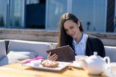 Mulher moreno nova no terraço em um café do verão que come o café da manhã com uma tabuleta em suas mãos foto de stock royalty free
