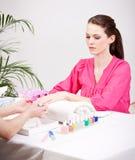 A mulher moreno nova obtém o tratamento de mãos no salão de beleza Foto de Stock