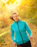 Mulher moreno nova que corre na floresta do outono que escuta os PM m Foto de Stock Royalty Free