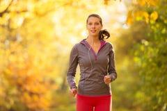 Mulher moreno nova que corre na floresta do outono que escuta os PM m Imagem de Stock