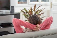 Mulher moreno nova que descansa no sofá fotografia de stock