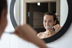 Mulher moreno nova que escova seus dentes na frente do espelho do banheiro fotos de stock