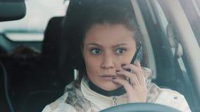 Mulher moreno nova que fala no telefone celular que senta-se no carro, nevando filme