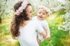Mulher moreno nova que guarda uma criança bonita Imagens de Stock
