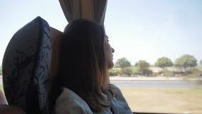 Mulher moreno nova que viaja pelo ônibus, admirando a vista através da janela