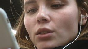 A mulher moreno nova usa um telefone com fones de ouvido filme