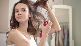 Mulher moreno que aplica o pulverizador de cabelo no banheiro Penteado da mulher na manhã video estoque