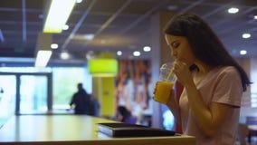 Mulher moreno que bebe o suco de laranja fresco de vidro plástico e que sorri, dieta video estoque